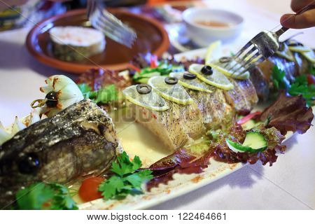Stuffed pike with lemon slices on the table