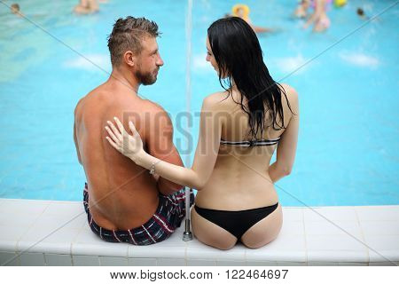 Tanned man and light-skinned woman in swimwear looking at each other sitting by the pool, view from the back
