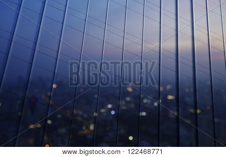 Reflection of blurred aerial view of cityscape on warm light sundown in metal wall of office building