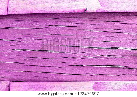 Horizontal orientation. The frame and copy space. purple and violet wooden rustic background or painted wood boards texture.  Cracks and crevices on the surface of the plywood.