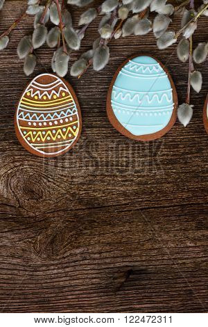 blue and brown eggs cookies and catkins on wooden background with copy space