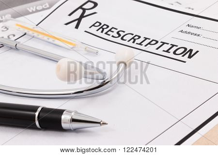 Closeup of red stethoscope thermometer and pen on a rx prescription.