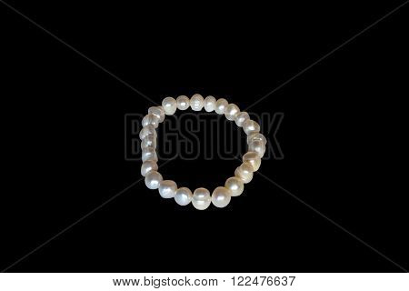 Bracelet of white sea pearls on a black background