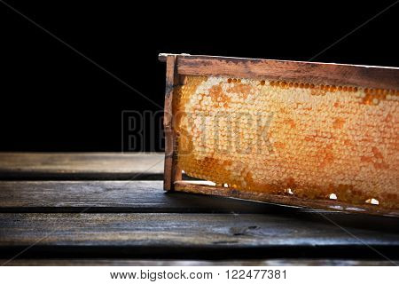 Wooden frame with honeycomb full of honey on wooden pallet isolated on black