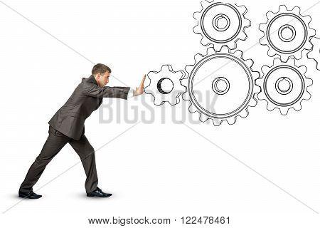 Businessman pushing cog wheels isolated on white background