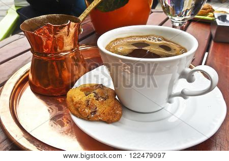 traditional greek coffee with coffee pot and cookie