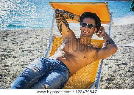 Young handsome man on beach laying on deckchair enjoying the place, smiling to camera. Seascape on background