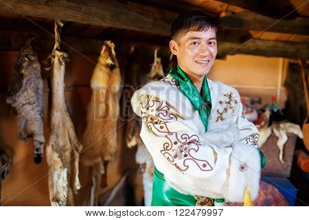Portrait of a male hunter in authentic traditional dress at the dwelling, animal hides in the background.