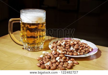 mug of beer and peanuts on the wooden table closeup