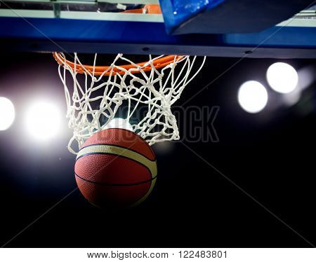 Basketball going through the hoop at a sports arena (intentional spotlight)
