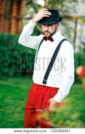 Macho man in a hat and red trousers with suspenders and bowtie.