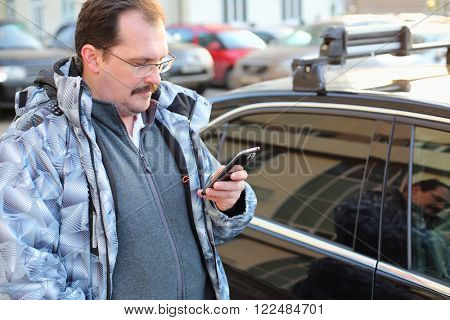 The man in glasses with mobile phone in hand near the car in the parking