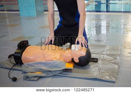 Instructor is sitting near mannequin - drowning in training center.