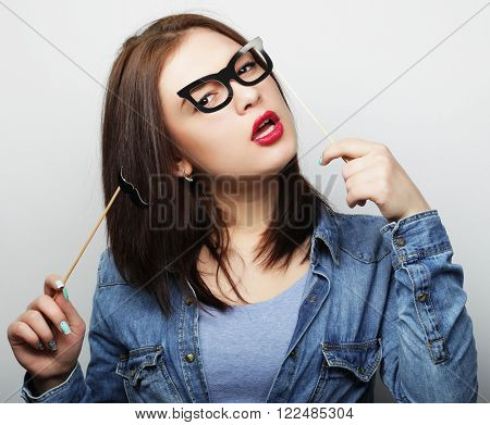 Party image. Playful young woman holding a party glasses.
