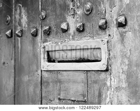 Ancient rusty iron letterbox opened on wooden door with metal ornaments black and white conversion intentionally blurred.