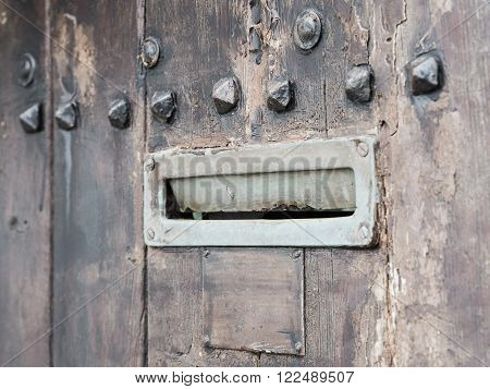 Ancient rusty iron letterbox opened on brown wooden door with metal ornaments intentionally blurred.