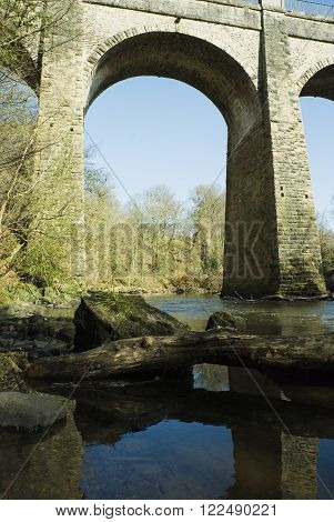 an image of a viaduct arch reflecting in the water of the river avon in scotland