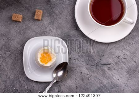 Healthy breakfast. Soft-boiled egg with tea on stone table