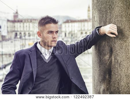 Handsome young man outdoor wearing jacket and shirt standing by historic building in European city. Turin, Italy