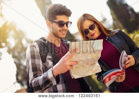 Couple of tourists looking at traveler's guide and a map