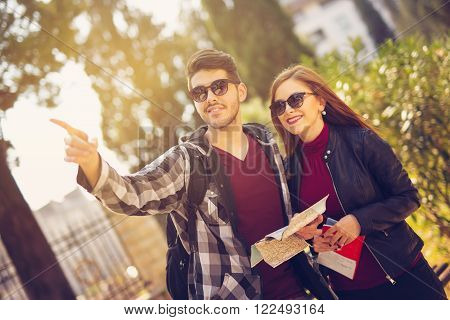 Couple of tourists looking at traveler's guide and a map ** Note: Shallow depth of field
