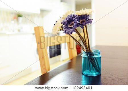 Purple and white gerberas bouquet in a blue vase on wooden table in the kitchen