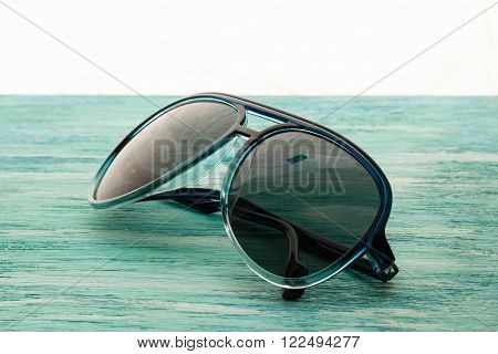 Stylish white sunglasses on the wooden background close up. horizontal  Stylish white  sunglasses on the wooden background close up. horizontal summer concept. the dismissal, blue background, holiday