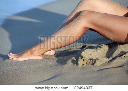 Female barefooted legs soiled in wet sand