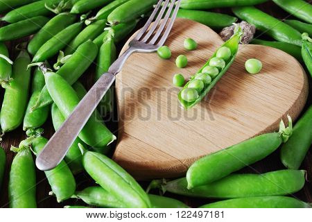 Pods of fresh green peas and wooden cutting board in the shape of a heart. Healthy food concept. Organic vegetables. Selective focus