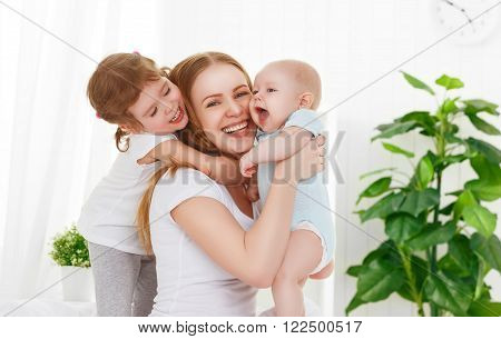happy family mother and two children son and daughter in bed playing