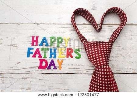 Happy fathers day sign and tie laid on wooden backround