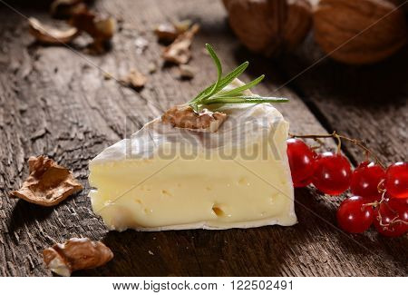 Brie cheese. Camembert cheese. Fresh Brie cheese with herbs and cranberry