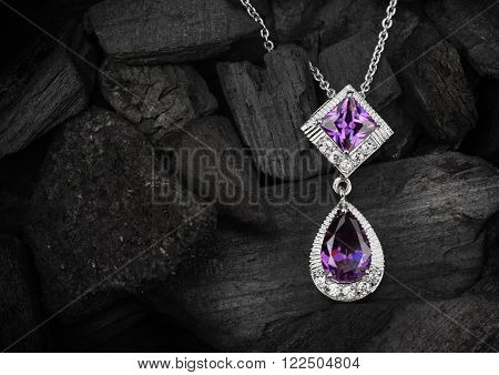 jewelry pendant witht gems on dark coal background
