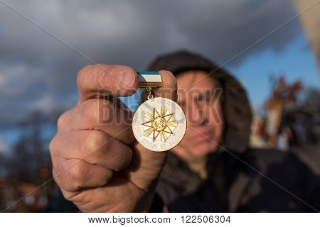 Saint-Petersburg Russia - March 18 2016: the rally on the occasion of the second anniversary of the reunion of Crimea to Russia Man shows a commemorative medal in honor of the liberation of Crimea