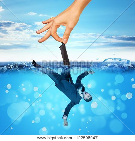Businessman drowning in sea with big hand holding for leg