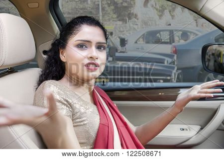 Young indian woman wearing traditional clothes and gets annoyed in a traffic jam