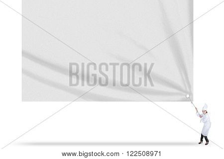 Portrait of happy female chef wearing uniform and drags a big empty banner in studio isolated on white background