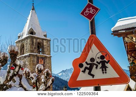 A boy and a girl playing on a roadsign close to a school with a snow-covered church and mountains in the background.