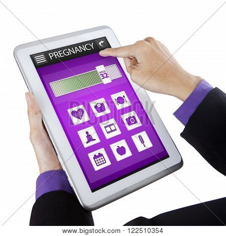 Close up of male hand holding a digital tablet with pregnancy applications on the screen isolated on white background