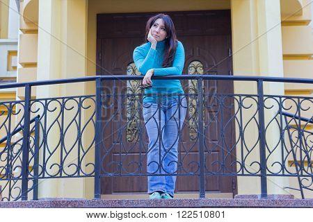 Beautiful girl in a blue turtleneck near the railing. People