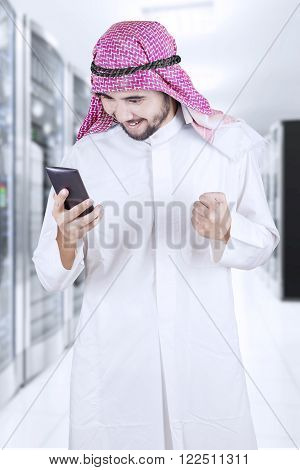 Muslim entrepreneur looks happy while reading a message on his mobile phone in the office