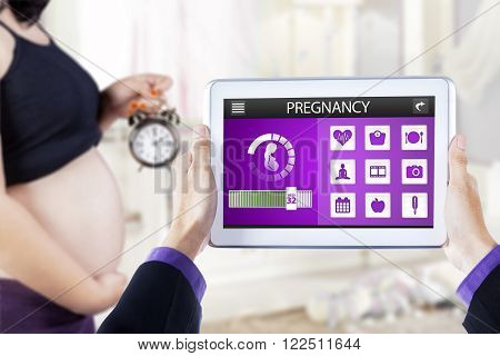 Close up of pregnant woman holding alarm clock at home, shot with pregnancy app on the tablet screen