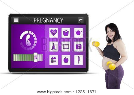 Portrait of pregnant woman doing workout with two dumbbells in front of pregnancy applications on the futuristic screen