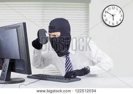 Picture of male robber wearing mask and looking for information with a magnifier on the computer in office
