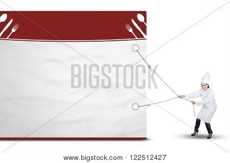 Image of female chef wearing a cooking wear and drags a big empty billboard isolated on white background