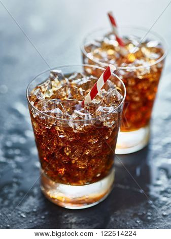 two glasses filled with ice and soda pop with striped straw