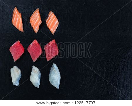 Overhead view of fresh Japanese sushi on black slate. Horizontal layout with plenty of copy space.