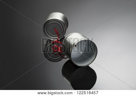 phone toy from a tin can lying on a smooth black polished table