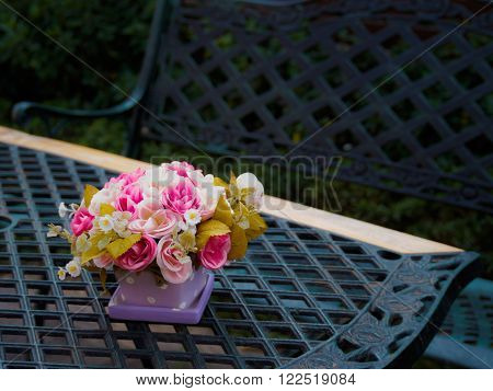 Flowerpot on vintage table and bench in outdoor garden and blurry background, Low Key