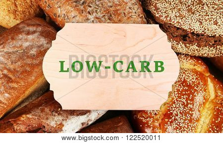 Text Low-Carb on wooden frame on bread background